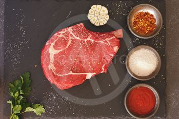 Fresh raw beef rib eye steak with seasoning, ready for...