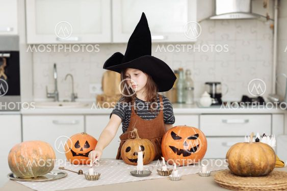 Happy halloween. Cute little girl in witch costume with...