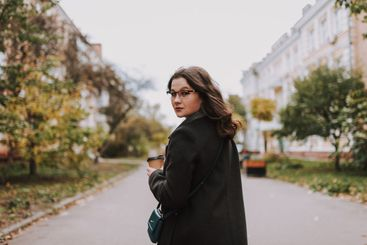 Beautiful lady walking in the city and turning back
