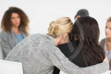 Women embracing in rehab group at therapy