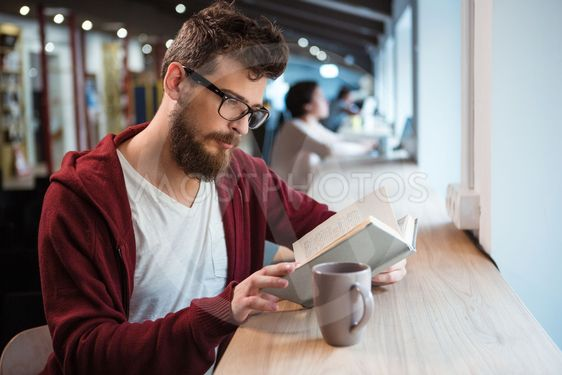 Clever boy in glasses reading  book sitting at the desk