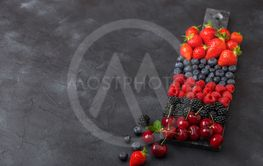 Fresh organic summer berries mix on black marble board...