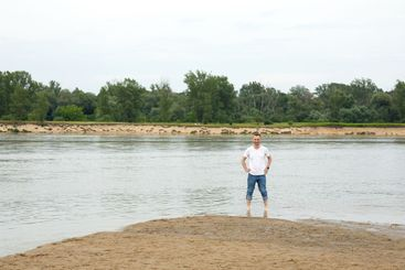 Lonely smiling man on a beach by the river