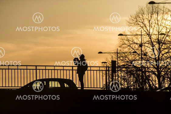 Silhouette of woman taking a photography on bridge with...