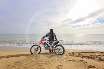 Biker sitting on a motorcycle on the beach