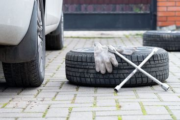 A wrench and work gloves lie on a winter car wheel lying...