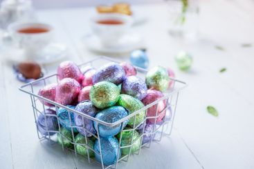 A metal modern basket filled chocolate easter eggs in...