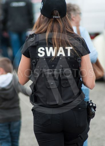 woman with swat police uniform walking on back view  at...