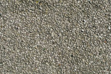 Old tarmac road stones close up texture background.