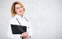 portrait of mature female doctor or nurse holding...