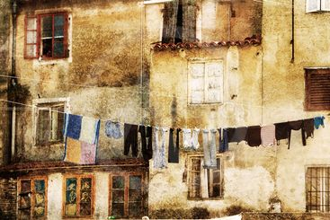 Laundry drying outside a weathered building.
