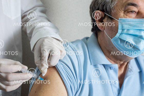 Doctor holding syringe with Covid-19 or coronavirus...