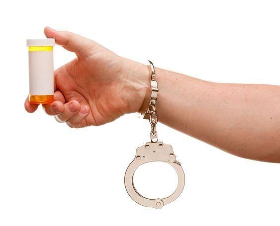 Handfängsel Man innehar tom medicin flaska isolerade på vit