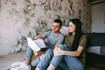 A young couple manages finances by looking through their...