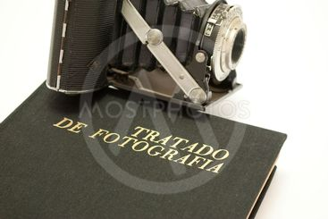 Old photo camera on book