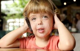 Cheerful toddler speaking on mobile phone