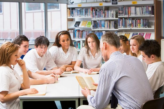 Schoolchildren and teacher studying in school library