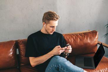 Focused caucasian man mobile developer in earphones...