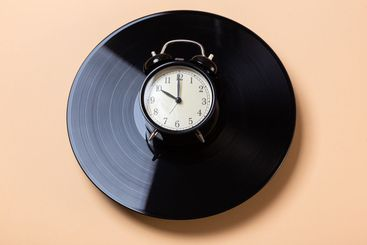 alarm clock lies on a vinyl record