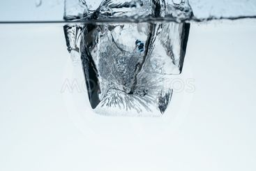 ice cube in water with splash, isolated on white