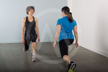 Smiling Middle Aged Sports Trainer Demonstrates Lunges