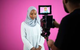 videographer in pink studio recording video on...