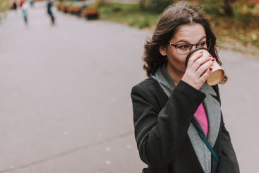 Calm lady with paper cup of coffee outdoors in her city