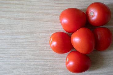 Group of fresh red tomatoes on a wooden table