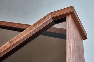Part of wooden steps with glass railings. Walnut staircase