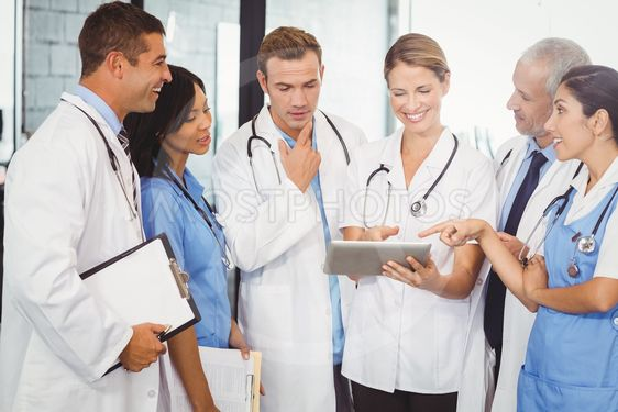 Medical team interacting and using digital tablet