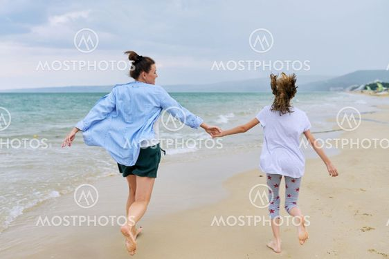 Happy mom and daughter running on the sea beach holding...