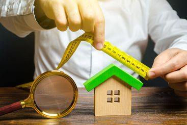 A man measures and evaluates a house. Fair value of real...
