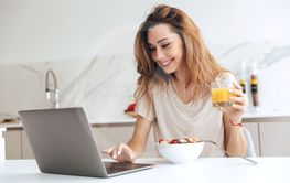 Positive woman with juice using laptop in the kitchen