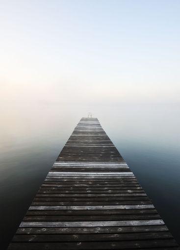 Wooden jetty in misty water, Sweden.