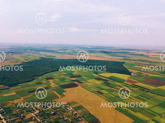 Photo made with drone above village near crop fields in...