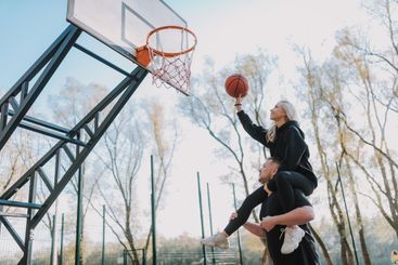 Happy young couple is playing basketball together