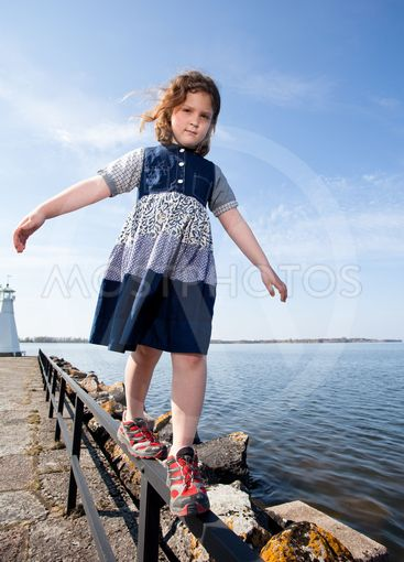 flicka balanserar på staket längs vattnet