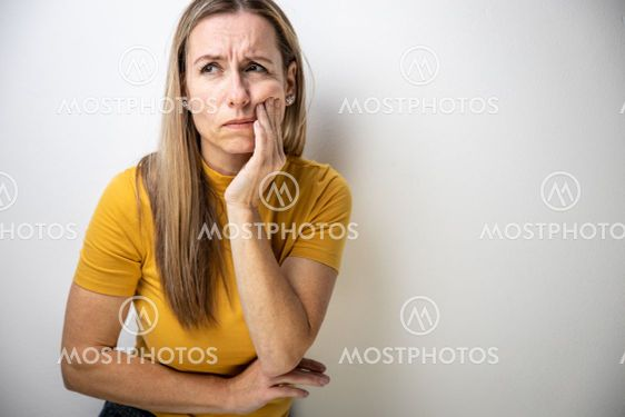Mid-aged woman touching her cheek/mouth with painful...