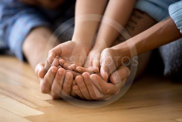 Family lying on floor together holding hands