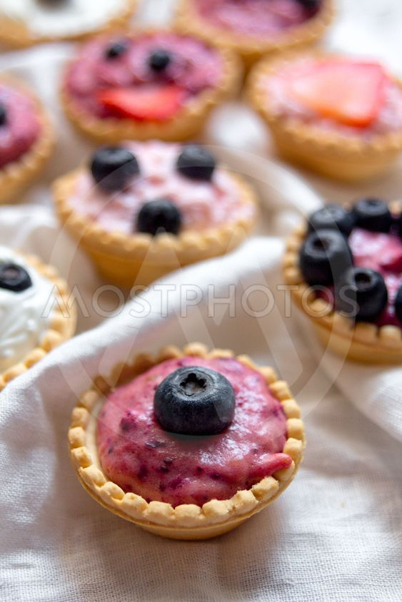 Sweet mini tartlets with cream and berries on white...