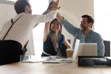 Overjoyed happy business team give high five at office...