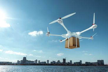 White flying drone with a cardboard box on a sky...