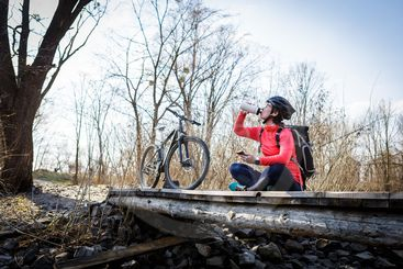 woman cyclist drinking water from a flask