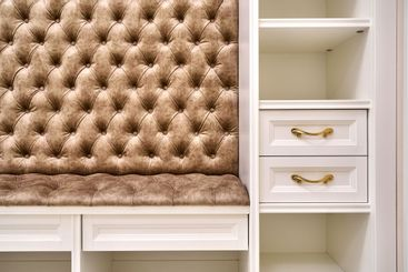 Classic white wardrobe with seating and shelves in...
