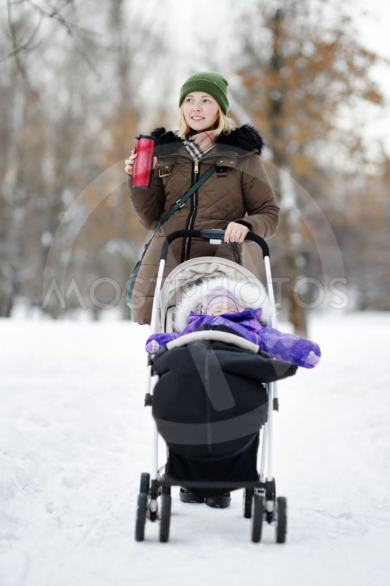 Young mother walking with baby in stroller in winter