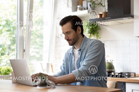 Millennial man look at laptop screen working online