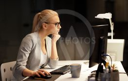 businesswoman at computer working at night office