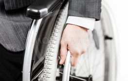 Invalid or disabled businessman in black suit sitting...