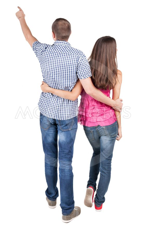 young couple pointing at wal Back view