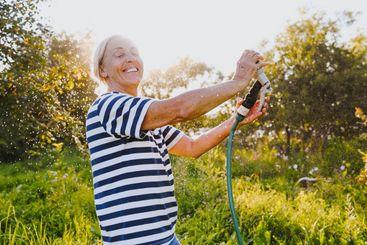 Happy elderly senior woman having fun watering plants...